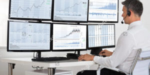 stock-photo-side-view-of-stock-market-broker-looking-at-graphs-on-multiple-screens-in-office-366442286